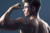 Rear view portrait of man flexing biceps muscles - Stock Image - CRBF6N