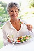 Senior Woman Eating An Al Fresco Lunch - Stock Image - B7JB77