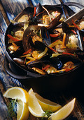 Mussels in white wine in pot with lemon wedges on the side, close-up - Stock Image - AWMJ27