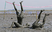 Brunsbuettel, Germany. 11th July, 2015. Partipants play volleyball during the Mud Olympics held at the North Sea coast in Brunsbuettel, Germany, 11 July 2015. Amateur athletes have competed in several disciplines at the Mud Olympics since 2004. Photo: AXEL HEIMKEN/dpa/Alamy Live News - Stock Image - EXCDRM