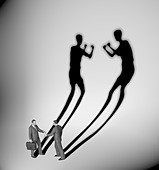 Two businessman casting a shadow shaped like two fighters - Stock Image - CX6NE2