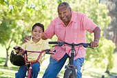 Grandfather and grandson on bikes outdoors smiling - Stock Image - B3K7A4