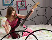 Young girls playing guitar on her bed - Stock Image - BNW53J
