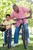 Grandfather and grandson on bikes outdoors smiling - Stock Image - B3K7DR