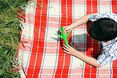 Boy playing with green toy plane - Stock Image - B2R93D