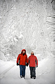 A couple in matching red winter coats walking in a Cotswold lane in snowy conditions UK - Stock Image - CEJEX4