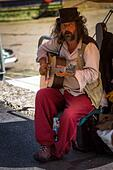 a musician busker playing acoustic guitar at Padstow Harbour in  Cornwall, UK - Stock Image - HEYKH3