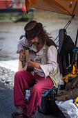 a musician busker playing acoustic guitar at Padstow Harbour in  Cornwall, UK - Stock Image - HEYKH2