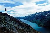 Hiker standing above Gjende (or Gjendin) Lake in the Jotunheimen mountains in Norway's Jotunheimen National Park - Stock Image - BEFK7F