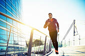 athlete with earphones running in the city - Stock Image - H7MHA3