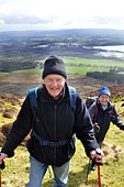 Active elderly people go hill walking in the Trossachs National Park, Scotland - Stock Image - BKW8G8