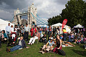 People gathering to hang out, listen to bands and other activities at the Blue Ribbon Village. Thames Festival London UK. - Stock Image - E7EF88