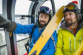 Male skiers talking in gondola in mountains - Stock Image - D7JNPW