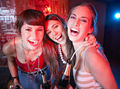 Three women in a nightclub drinking and laughing - Stock Image - B0K8F5