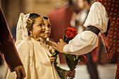 Valencia, Spain. March 18th, 2014: A little Fallera finally offers her flower bouquet to the Virgin and hands it over to be placed at the virgins image. © matthi/Alamy Live News - Stock Image - DX68R8