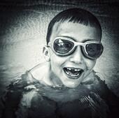 Smiling child with missing tooth in a swimming pool - Stock Image - S0FH5M
