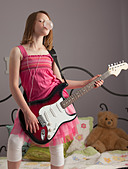 Young girls playing guitar on her bed - Stock Image - BNW54A