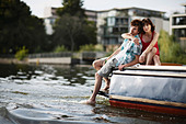 Germany, Berlin, Young couple sitting on motor boat, portrait - Stock Image - C5WFE2