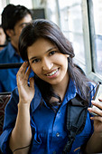 Female student listening to mp3 player on bus - Stock Image - A4WPBN