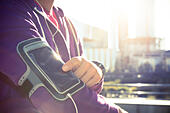 Running workout man listening to music with mp3 player armband or smart mobile phone. - Stock Image - H7MH9K