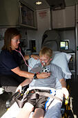 Female paramedic assisting young male patient in back of ambulance. - Stock Image - EXGX90