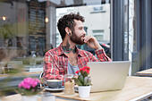 Young tattooed hipster using laptop outside cafe - Stock Image - H821H7