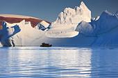 Cruising between the icebergs at Røde Ø, Scoresbysund, Greenland - Stock Image - CBY33R