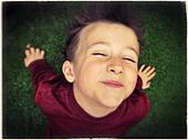 Portrait of a handsome boy with closed eyes on a grass - Stock Image - S0BCC5