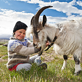 Girl with goat, Goat farm, Iceland - Stock Image - CBJ9YA