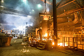 Steel workers watching furnace in steel foundry - Stock Image - DC1NCF