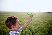 Boy playing with toy plane - Stock Image - B2R5JC