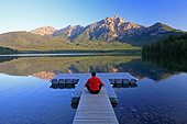 Middle age male meditating on dock at Pyramid Lake, Jasper National Park, Alberta, Canada. - Stock Image - CFBXN0