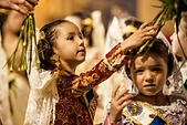 Valencia, Spain. March 18th, 2014: A little Fallera finally offers her flower bouquet to the Virgin and hands it over to be placed at the virgins image. © matthi/Alamy Live News - Stock Image - DX658E
