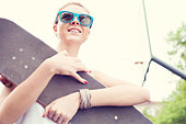 Young happy woman in blue sunglasses with a skateboard in her hands in the daytime. Outdoors - Stock Image - D8J34D