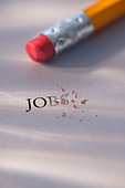 Studio shot of pencil erasing the word jobs from piece of paper - Stock Image - C3HK7P
