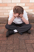 A MODEL RELEASED picture of an eleven year old boy looking depressed outdoors wearing his school uniform in the Uk - Stock Image - C2KC1H