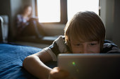 Boy using digital tablet on bed - Stock Image - FJX5RP