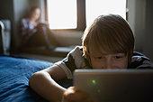 Boy using digital tablet on bed - Stock Image - FJX5RP
