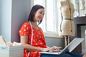 Female seamstress working on laptop in home studio - Stock Image - D7JH06