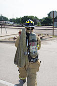 Female firefighter in rural volunteer fire department working with equipment. - Stock Image - EXHWME