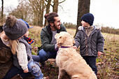 Family With Dog On Winter Walk Playing In Countryside - Stock Image - FWWCHM