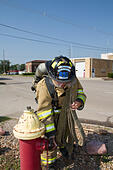Female firefighter in rural volunteer fire department working with equipment. - Stock Image - EXJ05H