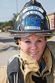 Female firefighter in rural volunteer fire department working with equipment. - Stock Image - EXJ1NP