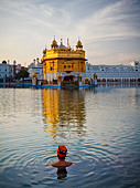 A Sikh man wearing a turban takes a bath in the pool surrounding the Golden Temple of Amritsar, Punjab, India - Stock Image - CF1G5B
