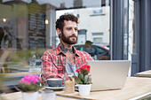 Young tattooed hipster using laptop outside cafe - Stock Image - H821HW