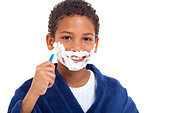 playful little african young boy shaving face over white background - Stock Image - DA05N5