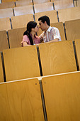 Students kissing in empty classroom - Stock Image - A75E8G