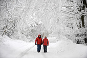 A couple in matching red winter coats walking in a Cotswold lane in snowy conditions UK - Stock Image - CEJEWG