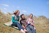 A young family having fun on the sand dunes at Horsey Beach on the Norfolk coast. - Stock Image - DYDCR5