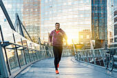 athlete with earphones running in the city - Stock Image - H7MHB8